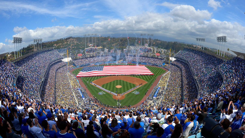 . Fans listen to the National Anthem during the Los Angeles Dodgers\' Opening Day baseball game against the San Francisco Giants at Dodger Stadium, Monday, April 1, 2013, in Los Angeles. (AP Photo/Mark J. Terrill)