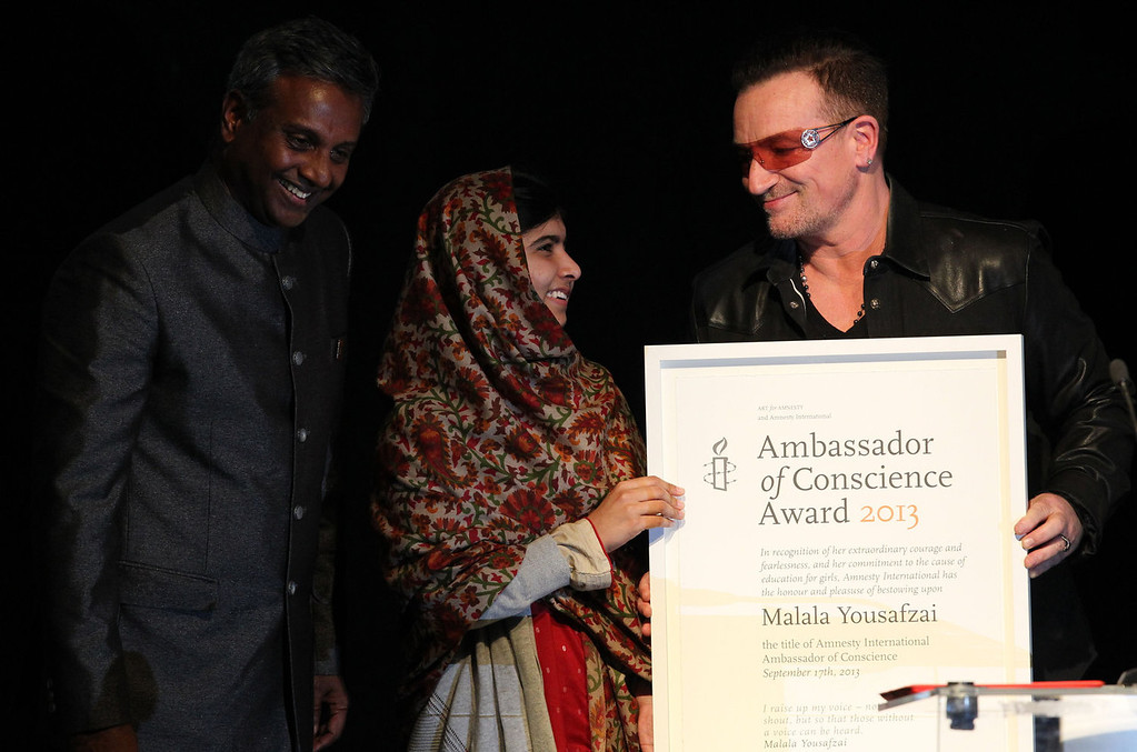 . Malala Yousafzai (C) receives the Amnesty International Ambassador of Conscience Award for 2013 from U2 singer Bono (R) as Salil Shetty, Secretary General of Amnesty International looks on during the Amnesty International Ambassador of Conscience Awards at the Manison House in Dublin, Ireland on September 17, 2013.  The Ambassador of Conscience Award is Amnesty International\'s highest honor, recognizing individuals who have promoted and enhanced the cause of human rights through their life and by example. Malala Yousafzai, 16, is an advocate for equal access to education. In 2012 she was shot and severely wounded in an attack claimed by the Pakistani Taliban.   PETER MUHLY/AFP/Getty Images