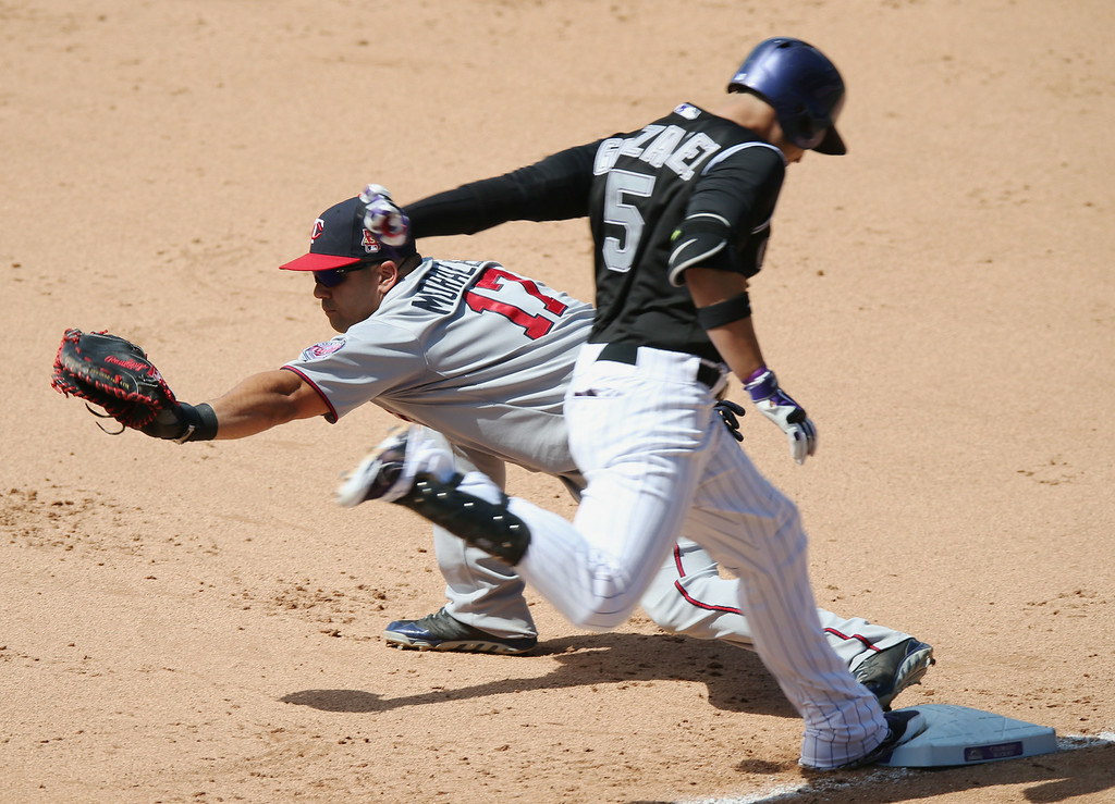 . Minnesota Twins first baseman Kendrys Morales, back, fields a throw to put out Colorado Rockies Carlos Gonzalez at first base after a dropped third strike in the fourth inning of an interleague baseball game in Denver on Sunday, July 13, 2014. (AP Photo/David Zalubowski)