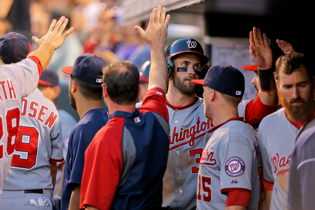 . DENVER, CO - JULY 22:  Bryce Harper #34 of the Washington Nationals celebrates in the dugout after scoring during the fifth inning against the Colorado Rockies at Coors Field on July 22, 2014 in Denver, Colorado.  (Photo by Justin Edmonds/Getty Images)