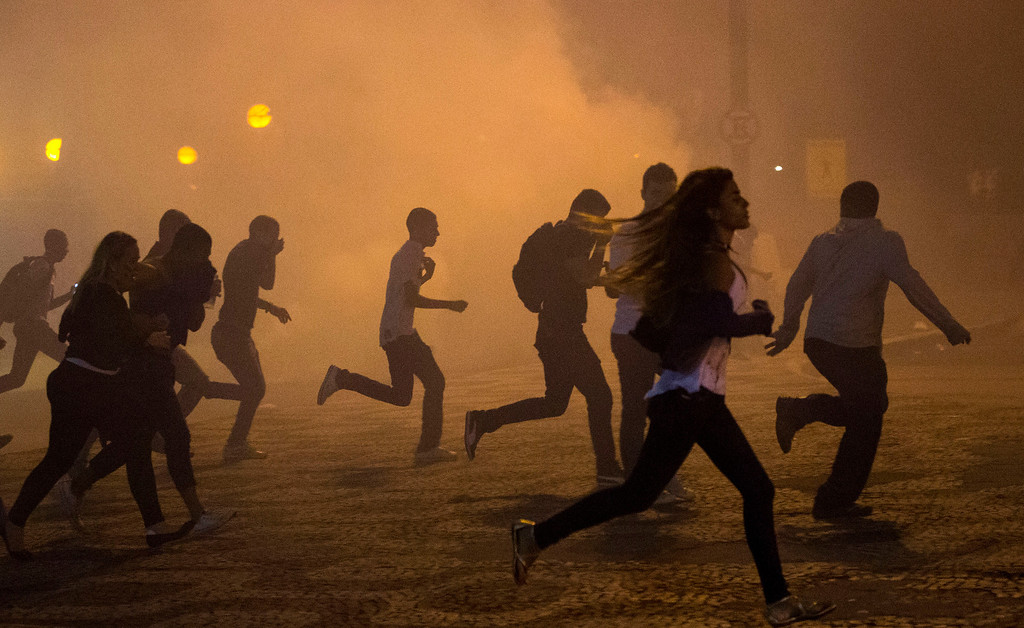 . Protesters run from the clouds of tear gas during an anti-government protest in Rio de Janeiro, Brazil, Thursday, June 20, 2013.  (AP Photo/Victor R. Caivano)