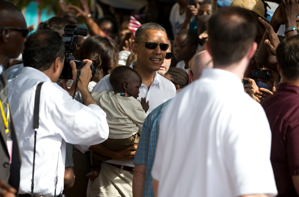 . White House photographer Pete Souza, left, takes photos of President Barack Obama as he holds a baby after taking a tour of Goree Island, Thursday, June 27, 2013, in Goree Island, Senegal. Goree Island is the site of the former slave house and embarkation point built by the Dutch in 1776, from which slaves were brought to the Americas. (AP Photo/Evan Vucci)