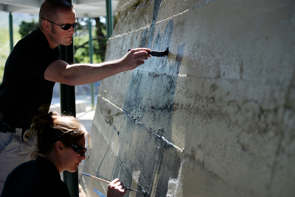 . Castle Rock police officer Renee Tremaine and Special Operations Seth Morrissey paint at Hangmans Gulch underpass June 9, 2014 along the Plum Creek trail. They plan on painting 12 underpasses throughout the town to help discourage graffiti. (Photo by John Leyba/The Denver Post)