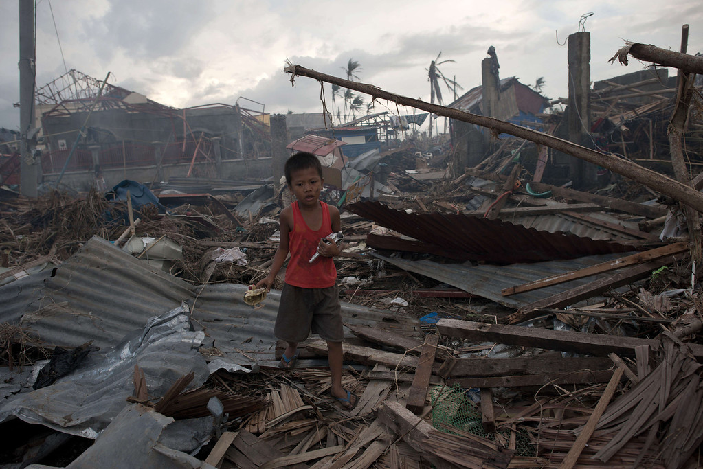 . A young typhoon survivor holds broken toys found amidst the rubble in Palo on November 21, 2013.  AFP PHOTO/ Nicolas ASFOURI/AFP/Getty Images