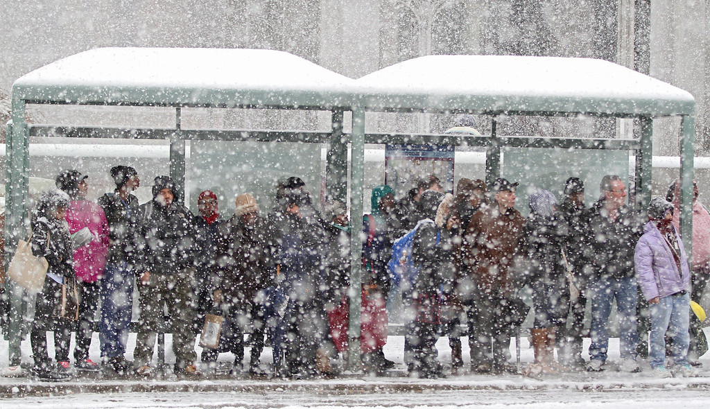 . People wait for buses as snow falls in Philadelphia on Tuesday, Jan. 21, 2014, at the beginning of a winter storm set to hit the northeast. (Michael Bryant/Philadelphia Inquirer/MCT)