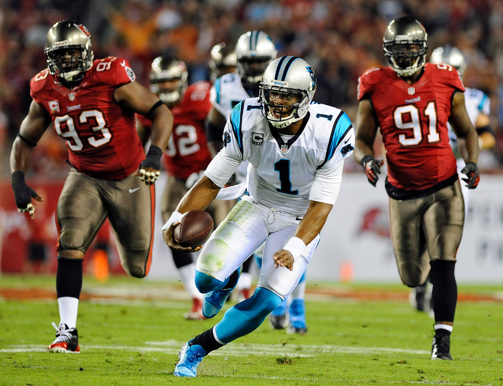 . Carolina Panthers quarterback Cam Newton (1) rushes past Tampa Bay Buccaneers defensive tackle Gerald McCoy (93) and defensive end Da\'Quan Bowers (91) during the first quarter of an NFL football game on Thursday, Oct. 24, 2013, in Tampa, Fla. (AP Photo/Brian Blanco)