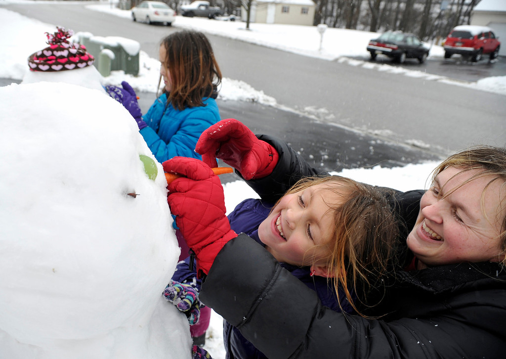 . Liz Dauberman helps her daughter Nicole, 7, insert a carrot into her snowman\'s head as Jessica, 10, works on her own snowman in their Shrewsbury, York County, Pa. front yard on Wednesday, March 6, 2013.    (AP Photo/York Daily Record,Chris Dunn )