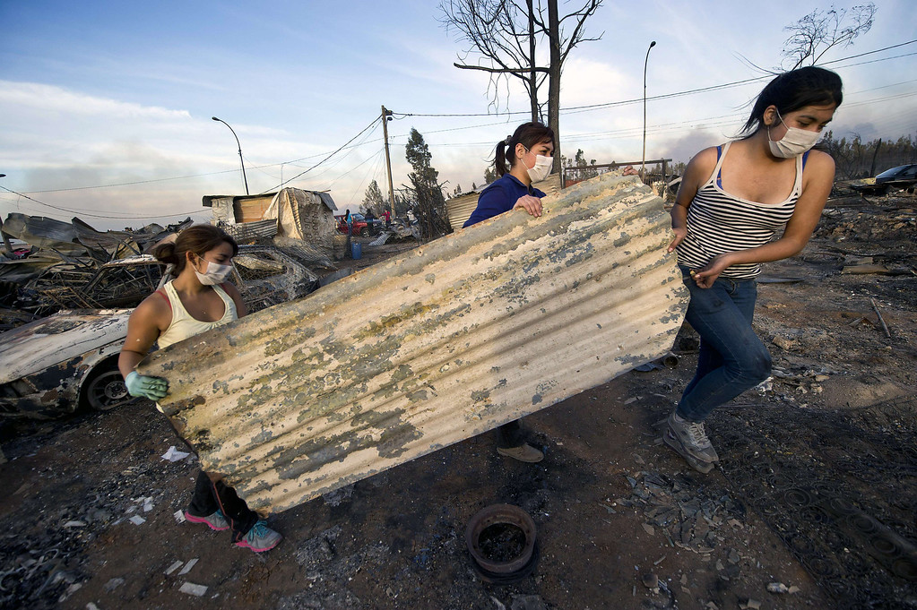 . Locals try to recover belongings in the area ravaged by fire, in Valparaiso, Chile, on April 13, 2014. More than 10,000 people were evacuated as an army of firefighters battled a killer blaze that --on the eve-- tore through parts of Chile\'s historic port of Valparaiso and left at least 11 people dead. The fire, which started in woodland Saturday, gutted 500 homes as flames advanced on the city of 270,000, famed for its UNESCO-listed center with cobblestone streets and brightly painted wooden homes. AFP PHOTO/MARTIN BERNETTI