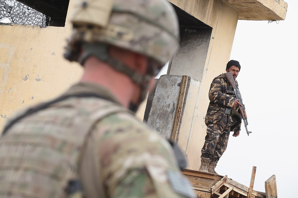 . A member of the Afghan National Security Forces stands guard during a visit by U.S. soldiers from the Army\'s 4th squadron 2d cavalry regiment at an outpost on February 25, 2014 near Kandahar, Afghanistan. Afghan National Security Forces have taken the lead in securing Afghanistan as the nation prepares for a drawdown of U.S. military support and the support of other nations in 2014.  (Photo by Scott Olson/Getty Images)
