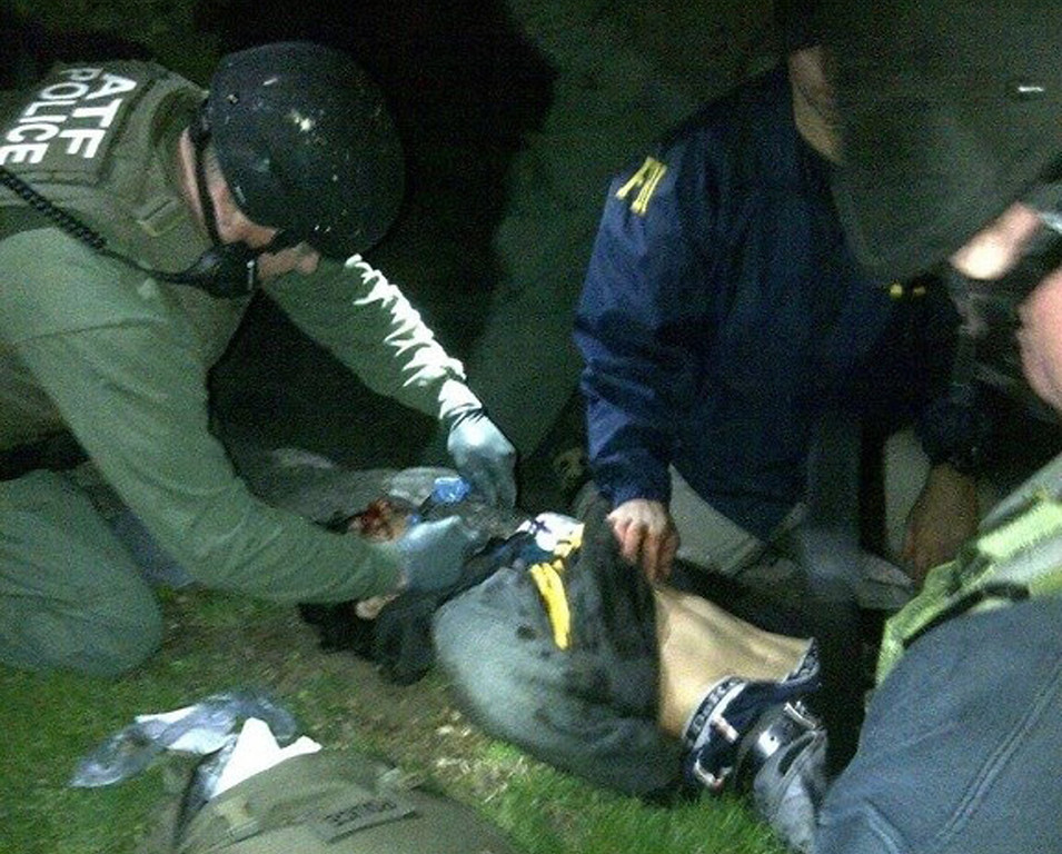 . In this Friday, April 19, 2013 photo obtained by The Associated Press and authenticated by a member of the Bureau of Alcohol, Tobacco, Firearms and Explosives, ATF and FBI agents check suspect Dzhokhar Tsarnaev for explosives and also give him medical attention after he was apprehended in Watertown, Mass., at the end of a tense day that began with his older brother, Tamerlan, dying in a getaway attempt. Tsarnaev lay hospitalized in serious condition under heavy guard Saturday as investigators continue piecing together the who and why of the two brothers involved in the deadly Boston Marathon bombings. (AP Photo)