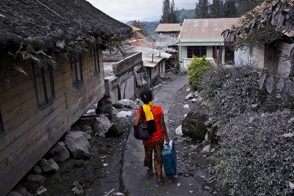 . Sumarni Br.Sitepu carries her belongings as she leaves her house in Mardinding village to a temporary evacuation center on November 15, 2013 in Karo district, South Sumatra, Indonesia.  (Photo by Ulet Ifansasti/Getty Images)