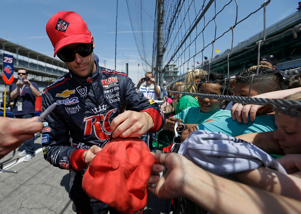 . Marco Andretti autographs souvenirs for school children during practice for the Indianapolis 500 auto race at the Indianapolis Motor Speedway in Indianapolis, Wednesday, May 15, 2013. (AP Photo/Darron Cummings)