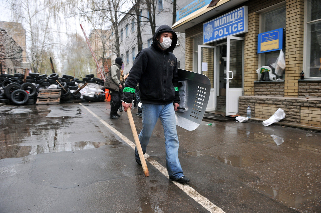 ". A pro-Russian activist, holding a wooden club and a shield, guards a barricade outside a regional police building seized by the armed separatists to prevent storming by the Ukrainian police special team in the eastern city of Slavyansk on April 13, 2014. Ukraine today launched an ""anti-terrorist operation\"" in Slavyansk, where pro-Russian gunmen have seized police and security services buildings, Interior Minister Arsen Avakov said. \""Units from all of the country\'s force structures are participating. May God be with us,\"" the minister wrote on his Facebook page. AFP PHOTO / GENYA SAVILOV"