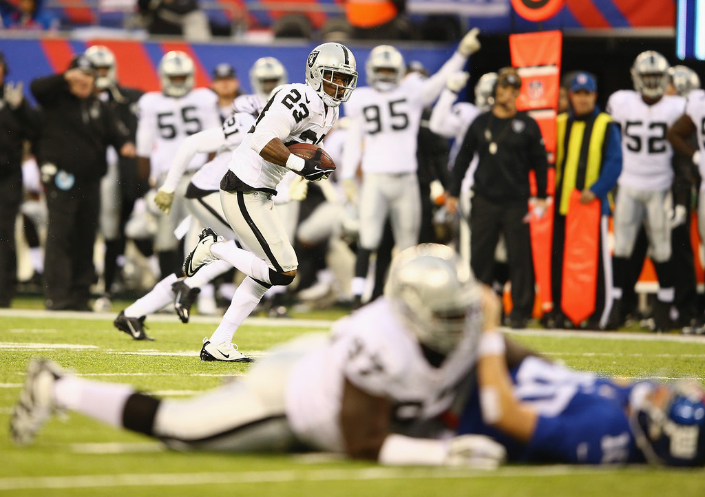 . Tracy Porter #23 of the Oakland Raiders runs for a touchdown after intercepting  Eli Manning #10 of the New York Giants who is in the foreground in the second quarter during their game at MetLife Stadium on November 10, 2013 in East Rutherford, New Jersey.  (Photo by Al Bello/Getty Images)