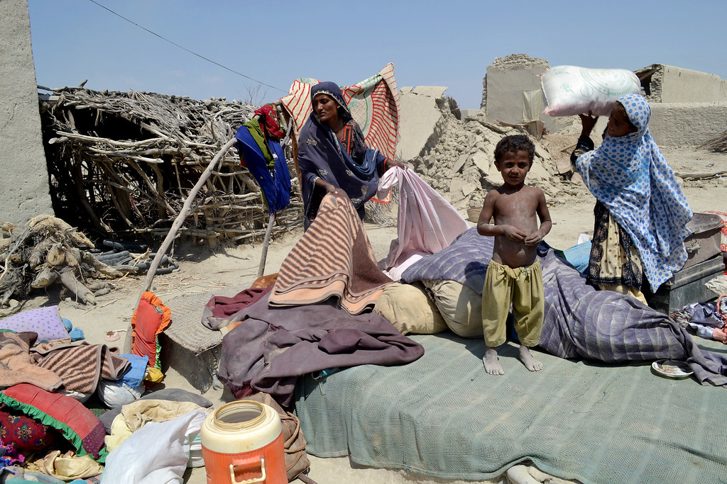 . Pakistani villagers collect belongings as their houses destroyed following an earthquake in Labach, the remote district of Awaran in Baluchistan province, Pakistan, Thursday, Sept. 26, 2013. (AP Photo/Arshad Butt)