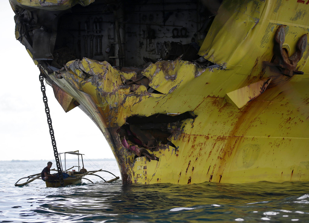 . A volunteer paddles close to the damaged bow of the cargo ship Sulpicio Express Siete Saturday Aug. 17, 2013, a day after it collided with the passenger ferry MV Thomas of Aquinas off the coast of Talisay city, Cebu province, in central Philippines. Divers combed through a sunken ferry Saturday to retrieve the bodies of more than 200 people still missing from an overnight collision with a cargo vessel near the central Philippine port of Cebu that sent passengers jumping into the ocean and leaving many others trapped. At least 28 were confirmed dead and hundreds rescued. The captain of the ferry MV Thomas Aquinas, which was approaching the port late Friday, ordered the ship abandoned when it began listing and then sank just minutes after collision with the MV Sulpicio Express, coast guard deputy chief Rear Adm. Luis Tuason said. (AP Photo/Bullit Marquez)