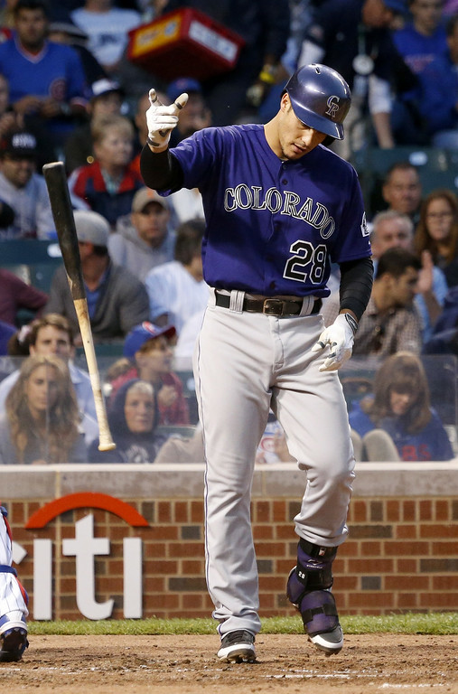 . Colorado Rockies\' Nolan Arenado slams his bat down after striking out on a pitch from Chicago Cubs\' Tsuyoshi Wada during the fourth inning of a baseball game Monday, July 28, 2014, in Chicago. (AP Photo/Charles Rex Arbogast)