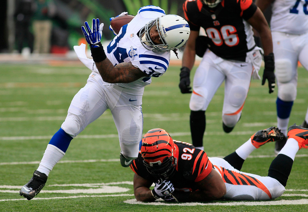 . Indianapolis Colts running back Trent Richardson (34) runs past Cincinnati Bengals outside linebacker James Harrison (92) in the first half of an NFL football game, Sunday, Dec. 8, 2013, in Cincinnati. (AP Photo/Tom Uhlman)