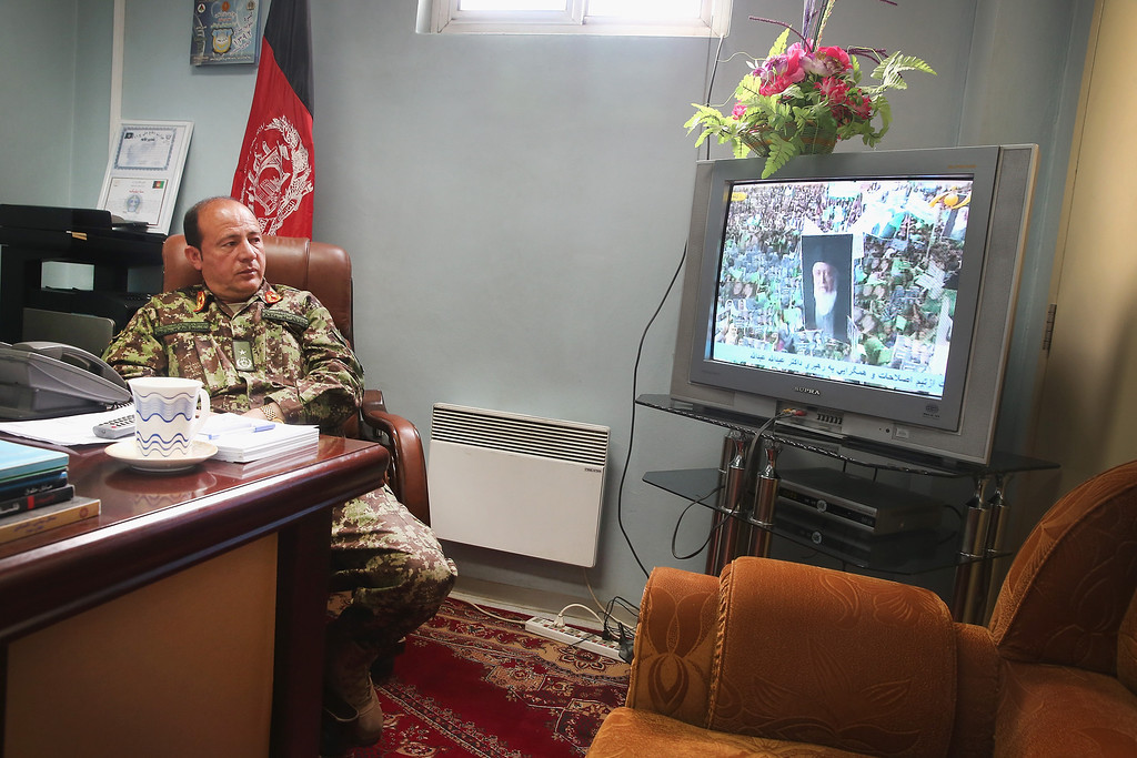 . GARDEZ, AFGHANISTAN - MARCH 24:  Brigadier General M. Asif Bromand Commander, Regional Medical Command-Southeast watches a rally for a presidential candidate on the television in his office at the Paktia Regional Military Hospital at Forward Operating Base (FOB) Thunder on March 24, 2014 near Gardez, Afghanistan. Afghans go to the polls to elect a new president on April 5th.The hospital, operated by the Afghan Army, treats wounded and sick soldiers and police from the Afghan National Security Forces (ANSF). Soldiers with the U.S. Army\'s 3rd Brigade Combat Team, 10th Mountain Division stationed at nearby FOB Lightning advise and assist the staff at the hospital.  (Photo by Scott Olson/Getty Images)