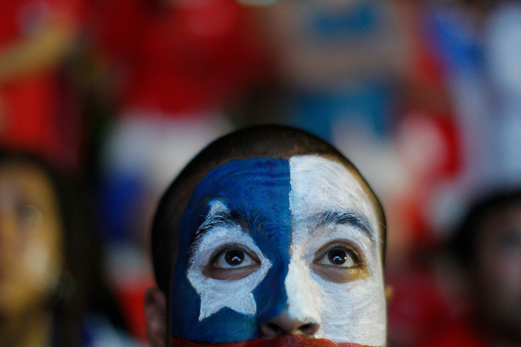 . A soccer fan with his face painted to represent the Chilean national flag, watches the live broadcast of the World Cup match between Chile and Australia, inside the FIFA Fan Fest area on Copacabana beach in Rio de Janeiro, Brazil, Friday, June 13, 2014. (AP Photo/Leo Correa)