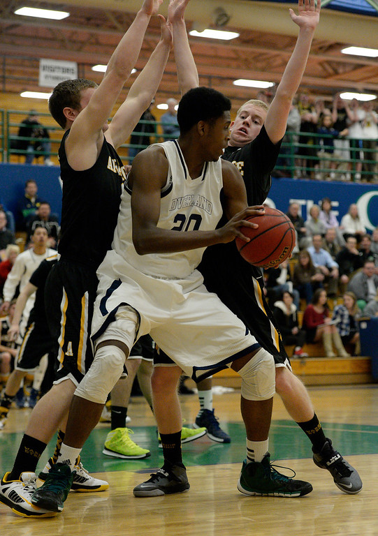 . AURORA, CO - FEBRUARY 12: Overland De\'Ron Daivs (20) gets double teamed by Arapahoe Ethan Brunhofer (11) and Brendan Till (13) during their 5A basketball game February 12, 2014 in Aurora. Overland defeated Arapahoe 72-65. (Photo by John Leyba/The Denver Post)