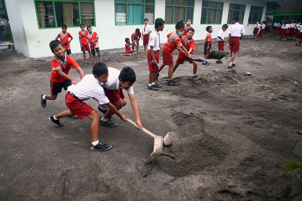 . Indonesian school children clear volcanic ash in their school grounds in Kediri, in East Java on February 17, 2014 following the eruption of Mount Kelud volcano on February 13 that killed four people and forced mass evacuations of residents.  AFP PHOTO/JUNI  KRISWANTO/AFP/Getty Images