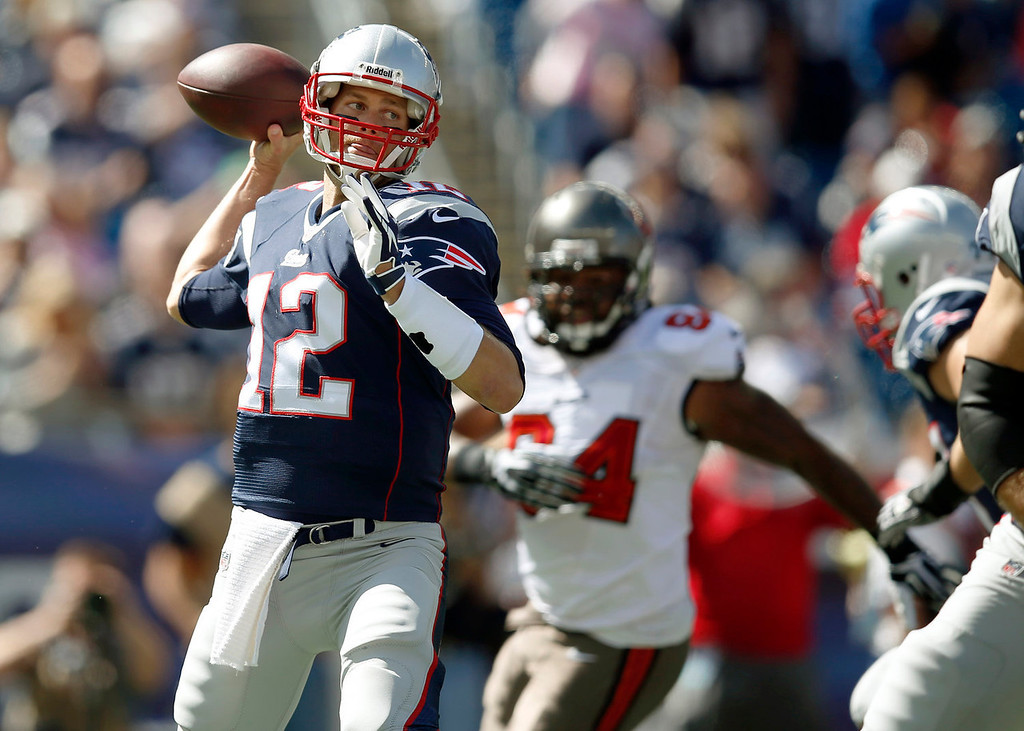. New England Patriots quarterback Tom Brady (12) passes while pursued by Tampa Bay Buccaneers defensive end Adrian Clayborn (94) in the first half of an NFL football game Sunday, Sept. 22, 2013, in Foxborough, Mass. (AP Photo/Elise Amendola)