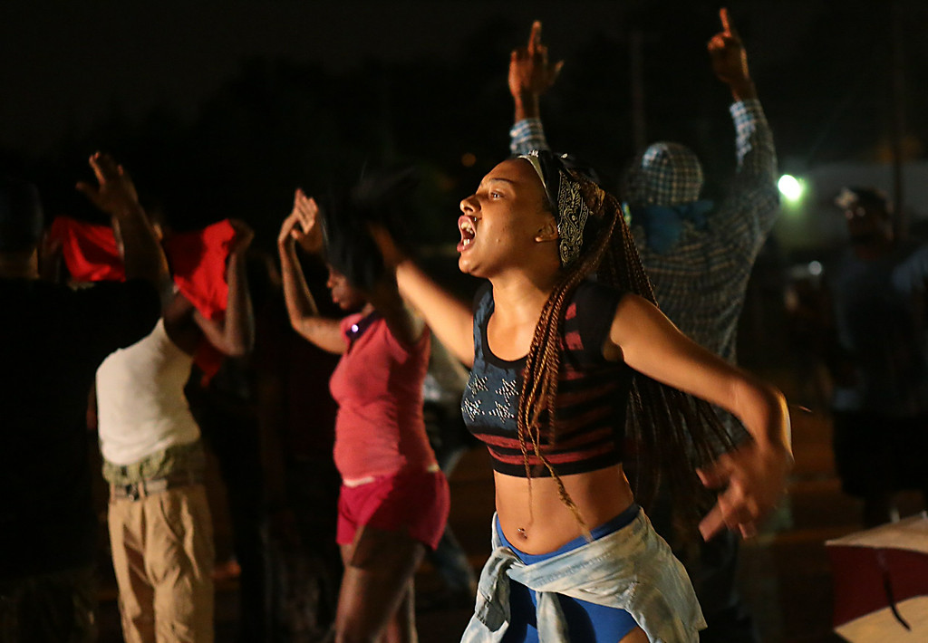 . Protestors stand in the middle of West Florissant Avenue in Ferguson, refusing to leave despite police orders early Saturday, Aug. 16, 2014. (AP Photo/St. Louis Post-Dispatch, Robert Cohen)