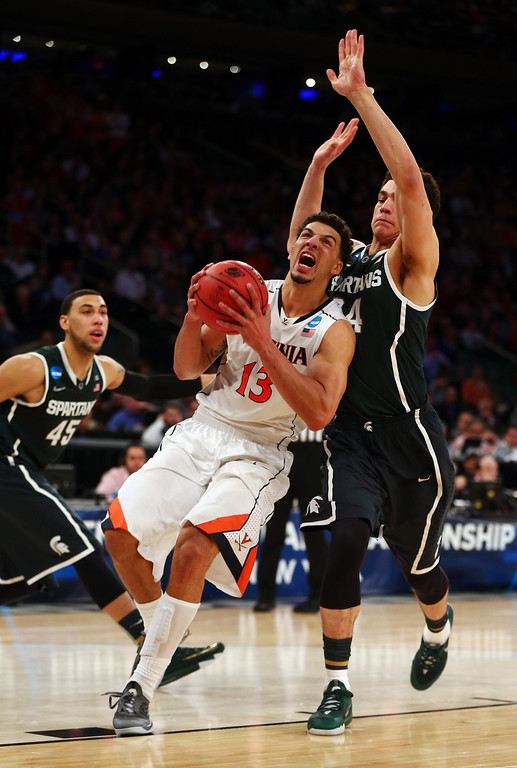 . Anthony Gill #13 of the Virginia Cavaliers handles the ball against Gavin Schilling #34 of the Michigan State Spartans during the regional semifinal of the 2014 NCAA Men\'s Basketball Tournament at Madison Square Garden on March 28, 2014 in New York City.  (Photo by Elsa/Getty Images)