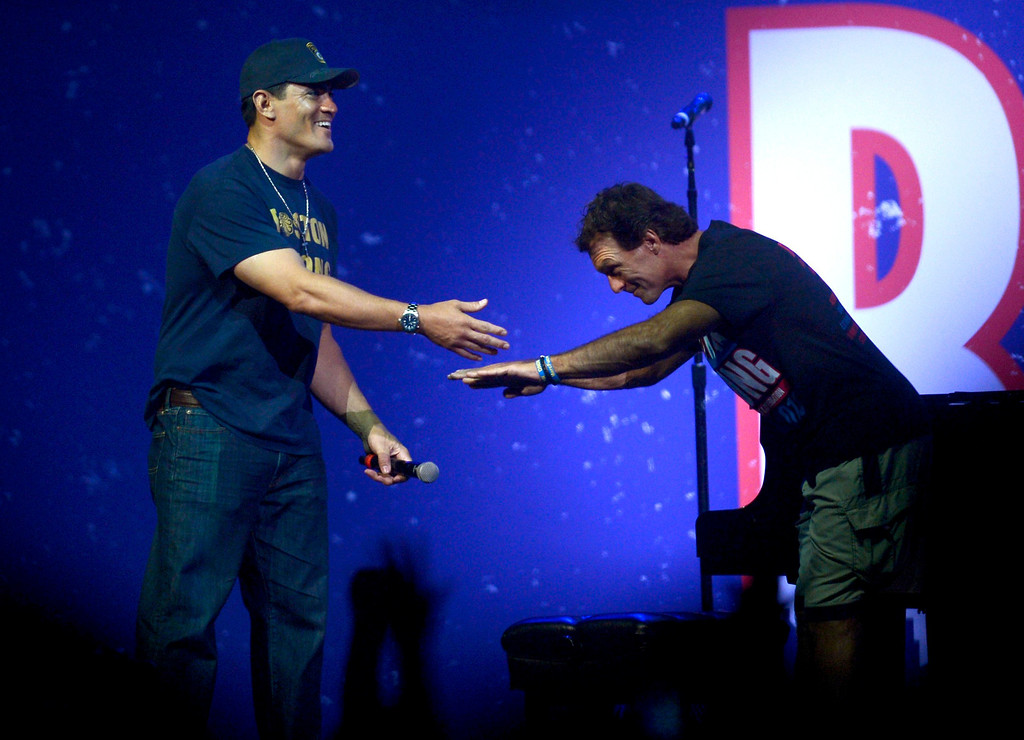 . Former football player and Massachusetts native Doug Flutie (R) bows to fellow former New England Patriot Tedy Bruschi during the Boston Strong benefit concert at the Boston TD Garden in Boston, May 30, 2013. REUTERS/Gretchen Ertl