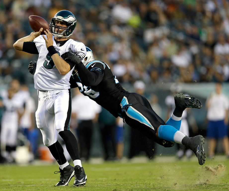 . Philadelphia Eagles quarterback Nick Foles, left, tries to pass under pressure from Carolina Panthers defensive end Greg Hardy during the first half of a preseason NFL football game, Thursday, Aug. 15, 2013, in Philadelphia. (AP Photo/Matt Rourke)