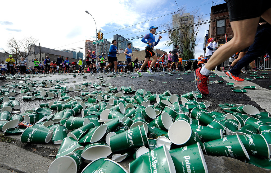 . Empty paper cups litter the street from runners quenching their thirst along Vernon Boulevard in the Queens borough of New York during the New York City Marathon on Sunday, Nov. 3, 2013. (AP Photo/Kathy Kmonicek)