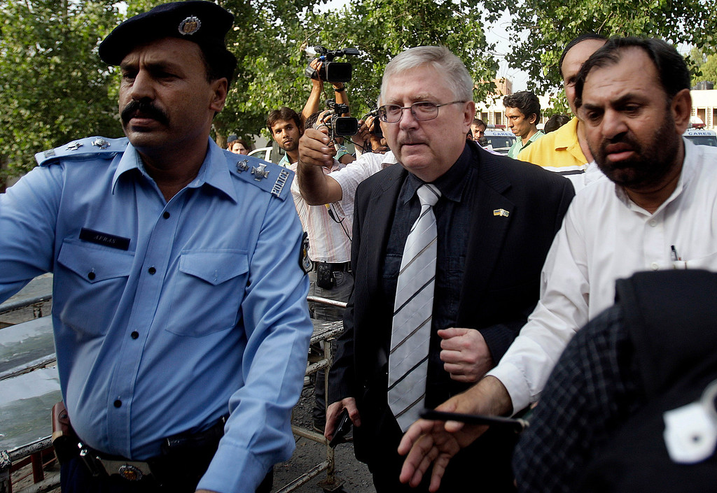 . A police officer makes way for Ukrainian Ambassador to Pakistan Volodymyr Lakomor, center, upon his arrival to see bodies of Ukrainian tourists, who were killed by Islamic militants, at a morgue of local hospital in Islamabad, Pakistan, Sunday, June 23, 2013. Islamic militants wearing police uniforms shot to death many foreign tourists and one Pakistani before dawn as they were visiting one of the worldís highest mountains in a remote area of northern Pakistan that has been largely peaceful, officials said. (AP Photo/Anjum Naveed)