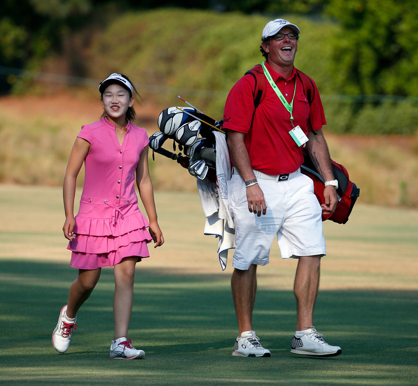 . Lucy Li, left, shares a laugh with her caddie as they walk to the second green during a practice round for the U.S. Women\'s Open golf tournament in Pinehurst, N.C., Wednesday, June 18, 2014. The sixth-grader from California is the youngest qualifier in the history of the U.S. Women\'s Open.(AP Photo/John Bazemore)