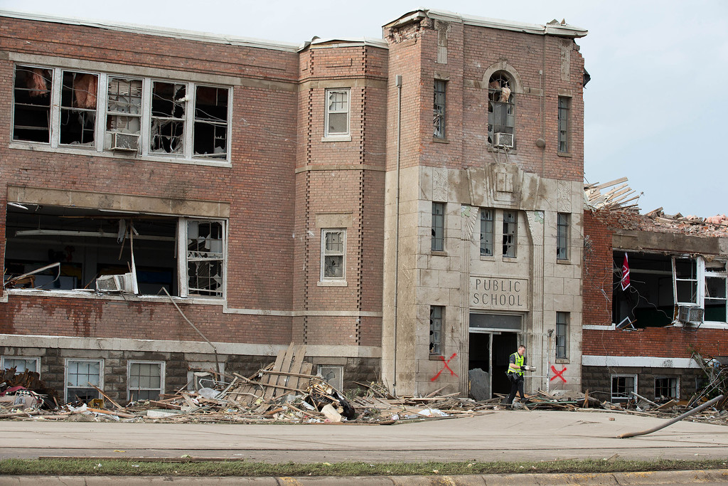 . A police officer exits the Wisner-Pilger Middle School after checking for people stuck inside Monday, June 16, 2014, in Pilger Neb. The National Weather Service said at least two twisters touched down within roughly a mile of each other. (AP Photo/The World-Herald, Ryan Soderlin)