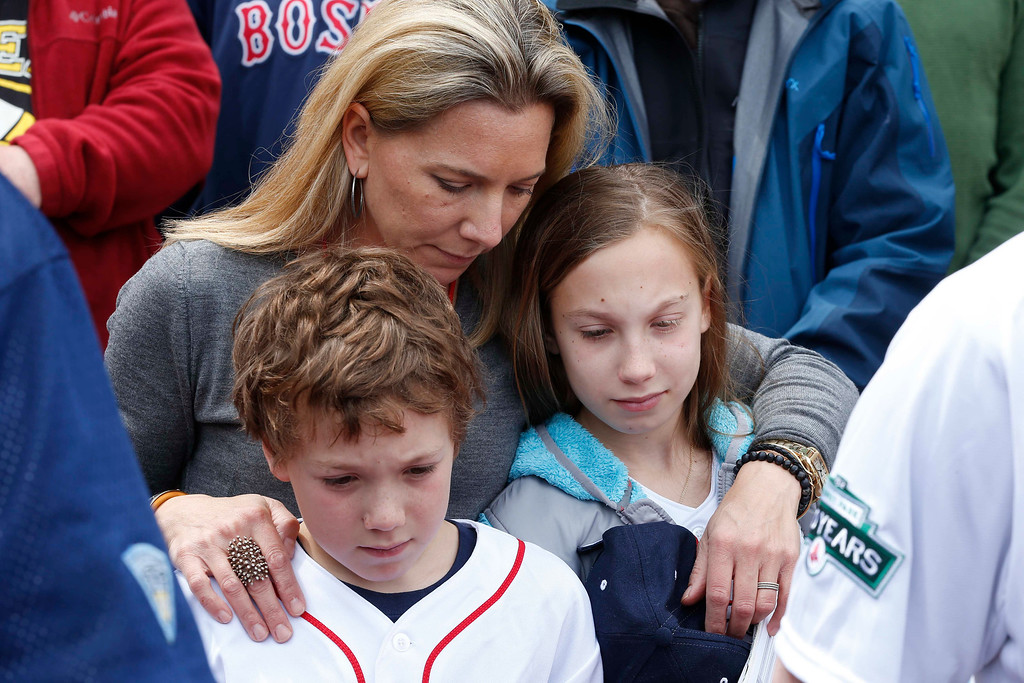 . A woman bows her head between two children during a moment of silence for the victims of the Boston Marathon bombings, before a baseball game between the Boston Red Sox and the Kansas City Royals in Boston, Saturday, April 20, 2013. (AP Photo/Michael Dwyer)