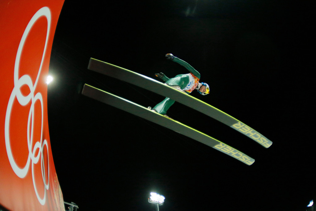 . In this photo taken with a fisheye lens Germany\'s Andreas Wellinger makes his trial jump during the ski jumping large hill qualification at the 2014 Winter Olympics, Friday, Feb. 14, 2014, in Krasnaya Polyana, Russia. (AP Photo/Dmitry Lovetsky)