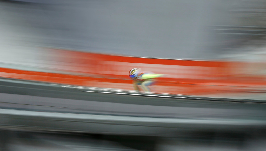 . In this photo taken with slow shutter speed an unidentified athlete starts an attempt during the men\'s normal hill ski jumping qualification at the 2014 Winter Olympics, Saturday, Feb. 8, 2014, in Krasnaya Polyana, Russia. (AP Photo/Matthias Schrader)