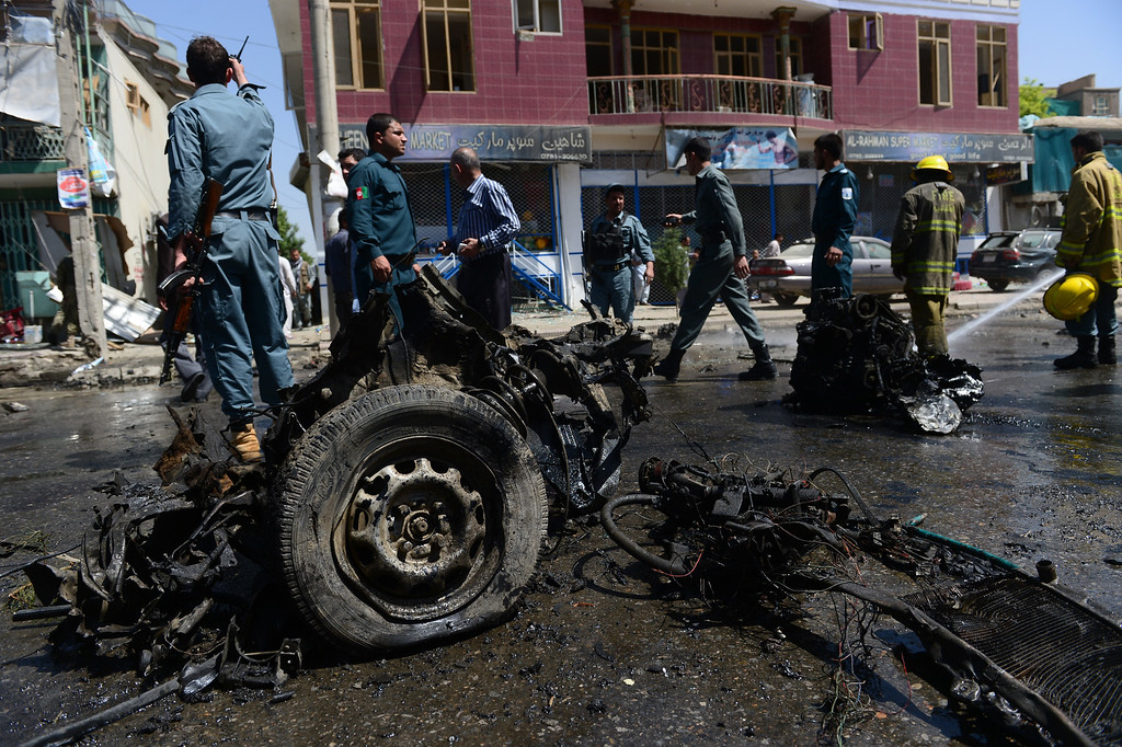 . Afghan policemen walk around the destroyed suicide car bomb at the site of a suicide attack in Kabul on May 16, 2013.  AFP PHOTO/ Massoud HOSSAINI/AFP/Getty Images