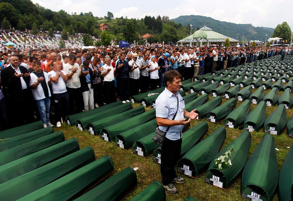 . Bosnians pray in front of 409 coffins of newly identified victims of the 1995 Srebrenica massacre in Potocari Memorial Center, near Srebrenica July 11, 2013. The bodies of the recently identified victims will be transported to the memorial centre in Potocari where they will be buried on July 11 marking the 18th anniversary of the massacre in which Bosnian Serb forces commanded by Ratko Mladic killed up to 8,000 Muslim men and boys and buried them in mass graves. REUTERS/Dado Ruvic
