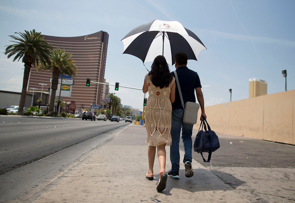 . Under the shade of an umbrella with temperatures already in triple digits by mid morning, tourists walk north along Las Vegas Boulevard toward The Strip, Sunday, June 30, 2013 in Las Vegas. Temperatures were on the rise again after the city reported a record overnight low of 89 degrees Sunday and forecasters predicting a high of 116.  (AP Photo/Julie Jacobson)