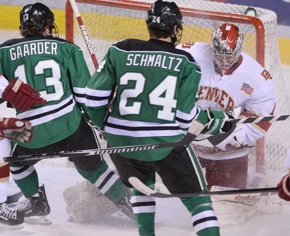 . DENVER, CO. - JANUARY 24:  Denver goalie Sam Brittain held onto the puck after making a save in the first period. North Dakota\'s center Connor Gaarder (13) and defenseman Jordan Schmaltz (24) looked for a rebound. The University of Denver hockey team hosted North Dakota at Magness Arena Friday night, January 24, 2014. Photo By Karl Gehring/The Denver Post