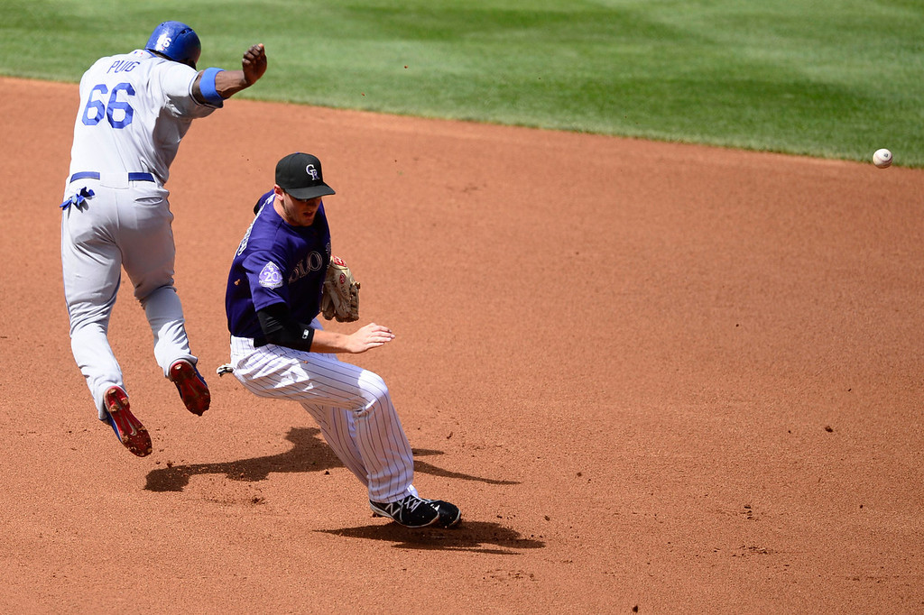 . Yasiel Puig (66) of the Los Angeles Dodgers collides with DJ LeMahieu (9) of the Colorado Rockies during the action in Denver on Monday, September 2, 2013. The Colorado Rockies hosted the Los Angeles Dodgers at Coors Field.   (Photo by AAron Ontiveroz/The Denver Post)