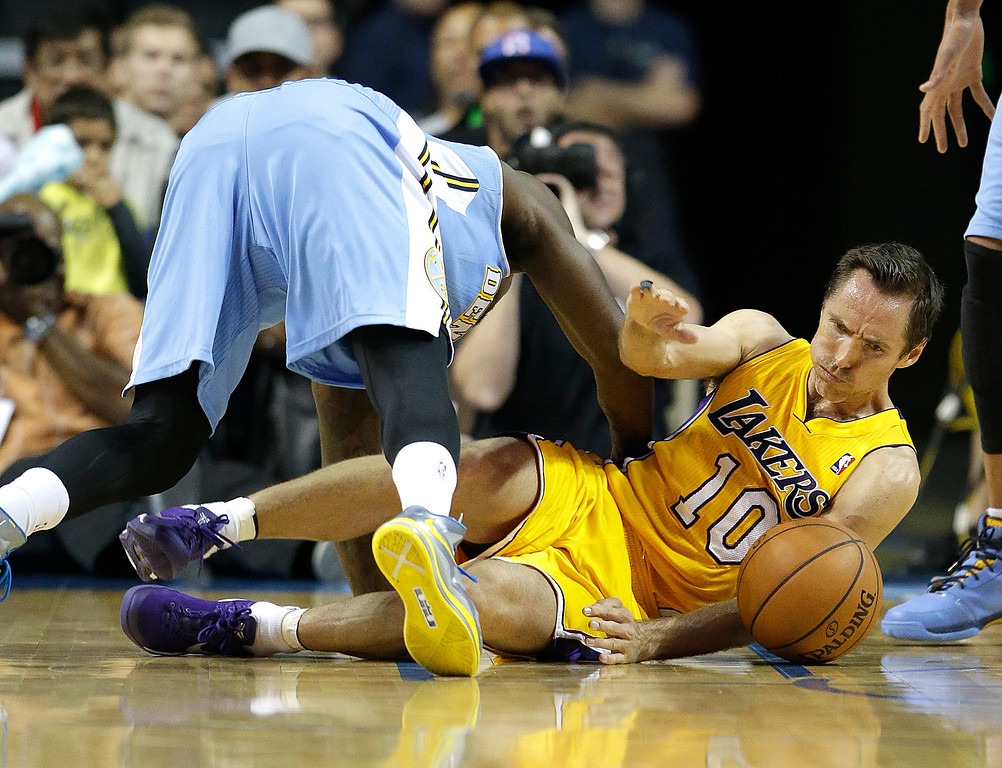 . Denver Nuggets\' Randy Foye, top, and Los Angeles Lakers\' Steve Nash fall to the court as they fight for a loose ball in the second half of an NBA preseason basketball game on Tuesday, Oct. 8, 2013, in Ontario, Calif. The Lakers won 90-88. (AP Photo/Jae C. Hong)