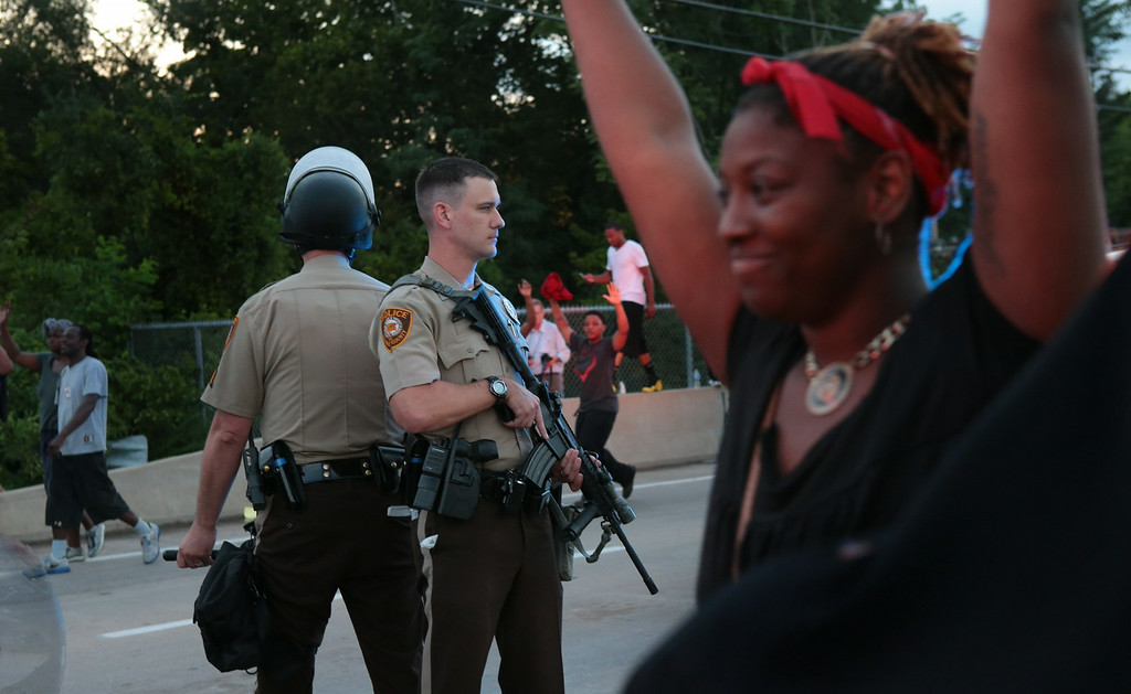 . St. Louis County police officers stand back to back as they attempt to move a crowd gathered in front of the QuikTrip, Monday, Aug. 11, 2014, in Ferguson, Mo. Authorities in Ferguson used tear gas and rubber bullets to try to disperse a large crowd Monday night that had gathered at the site of a burned-out convenience store damaged a night earlier, when many businesses in the area were looted. (AP Photo/St. Louis Post-Dispatch, Robert Cohen)
