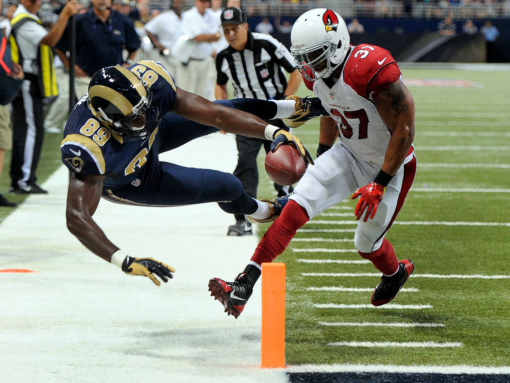 . St. Louis Rams tight end Jared Cook, left, dives into the end zone after catching a 16-yard pass for a touchdown as Arizona Cardinals safety Yeremiah Bell defends during the second quarter of an NFL football game on Sunday, Sept. 8, 2013, in St. Louis. (AP Photo/L.G. Patterson)