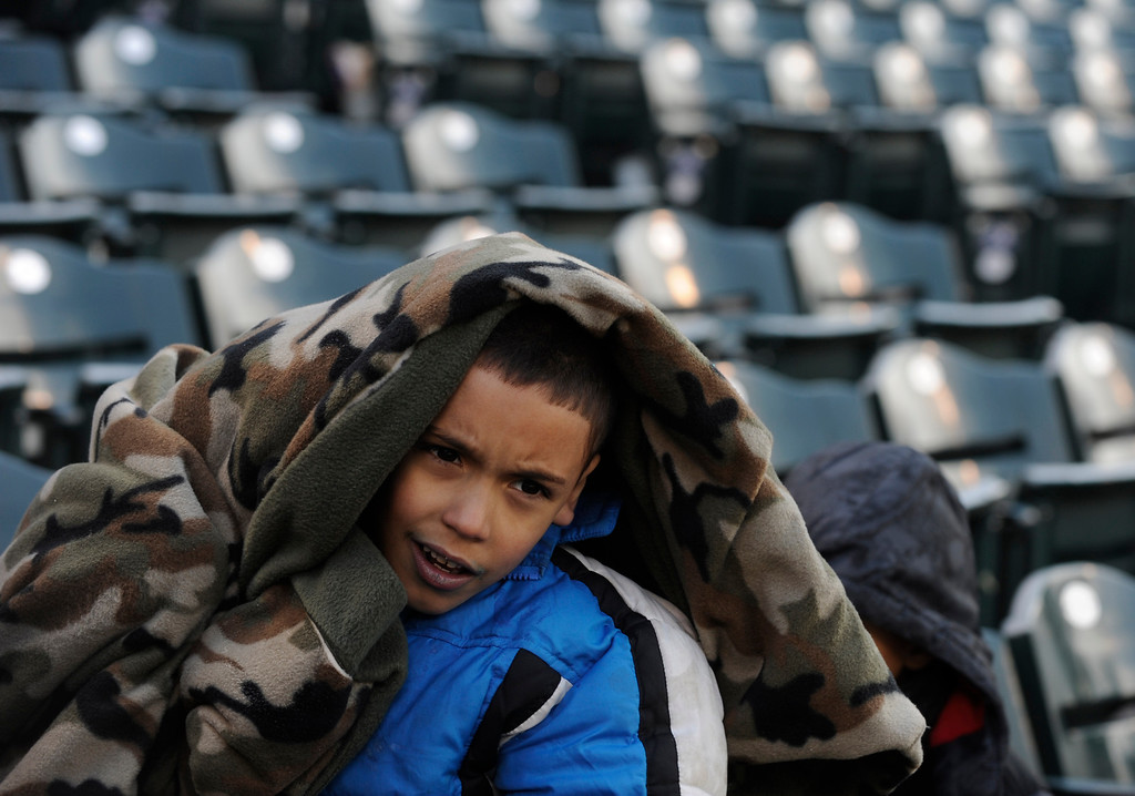 . DENVER, CO. - APRIL 23:  Christopher Henry Jr., age 7, shivered under a blanket as the Atlanta Braves defeated the Colorado Rockies 4-3 at Coors Field Tuesday, April 23, 2013.  The first game of the doubleheader Tuesday was a make-up from Monday night\'s postponement due to weather.  The temperature never climbed above freezing during the game. Photo By Karl Gehring/The Denver Post