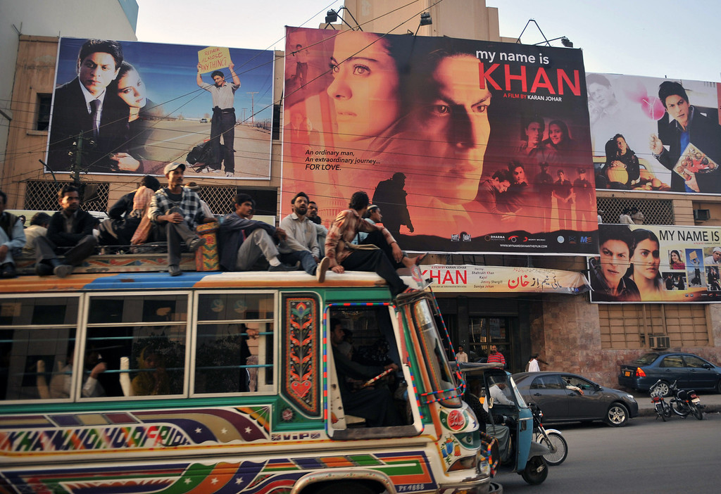 . Pakistani commuters, sitting on top of a bus, pass by a cinema screening Indian Bollywood actor Shah Rukh Khan\'s film \'My Name is Khan\' in Karachi on February 12, 2010. Cinemas in the Indian city of Mumbai scaled back the release on February 12 of top actor Shah Rukh Khan\'s new film, in the face of violent threats from right-wing Hindus locked in a row with the Bollywood star. The Shiv Sena, which pushes a regionalist, often anti-Muslim, anti-Pakistan agenda, has been outraged at Khan\'s comments regretting the absence of Pakistani cricketers from next month\'s Indian Premier League tournament. The 44-year-old Muslim actor, born in New Delhi to parents from what is now Pakistan, part-owns IPL outfit the Kolkata Knight Riders. RIZWAN TABASSUM/AFP/Getty Images