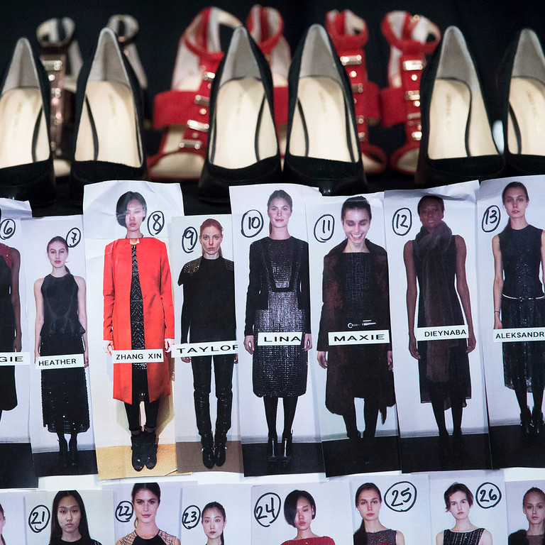 . Shoes rest on a table beside a look board backstage before the Carmen Marc Valvo Fall 2014 collection is modeled during Fashion Week, Friday, Feb. 7, 2014, in New York. (AP Photo/John Minchillo)