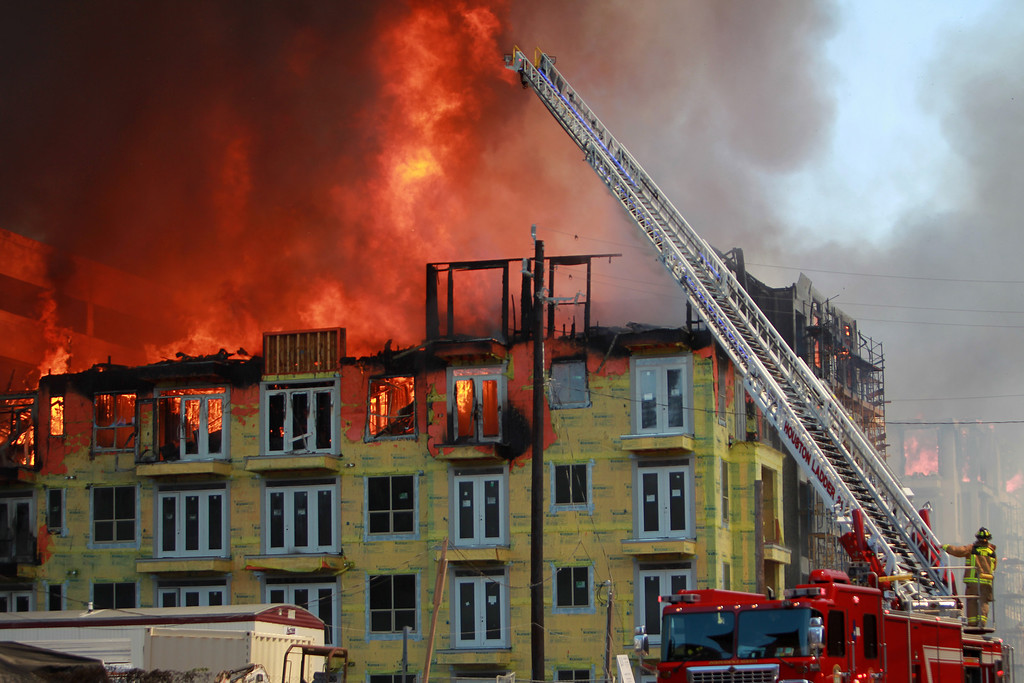 . Houston firefighters work to extinguish a five-alarm fire at a construction site Tuesday, March 25, 2014, in Houston. Fire officials said more than 200 emergency personnel were at the scene Tuesday afternoon and were working to protect nearby buildings. (AP Photo/Houston Chronicle, Mayra Beltran)